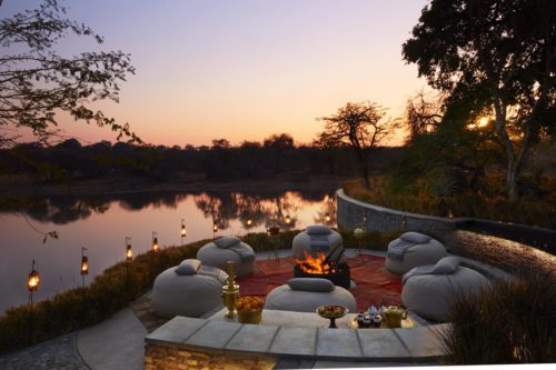ring of chairs around a fire with water in the background at sunset