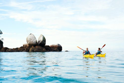 Two kayakers paddle toward Split Apple Rock in Abel Tasman National Park on New Zealand safari