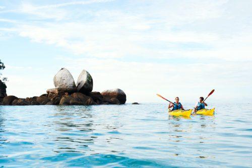 Two kayakers paddle toward Split Apple Rock in Abel Tasman National Park on New Zealand safari