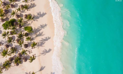 aerial view of Zuri Zanzibar's white sandy beach dotted with shade umbrellas and aqua waters