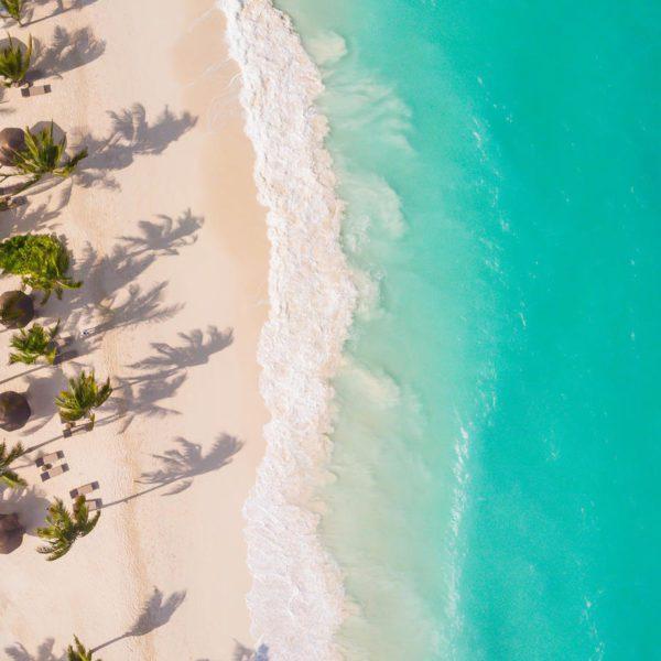 aerial view of Zuri Zanzibar's white sandy beach dotted with shade umbrellas and aqua waters
