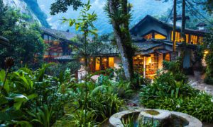 lodge lit up with green plants in foreground in Peru