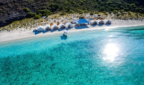 crystal clear water with white sand beach and tents set up