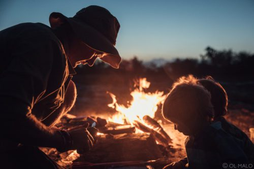 man and boy leaning over a fire at night while they visit kenya