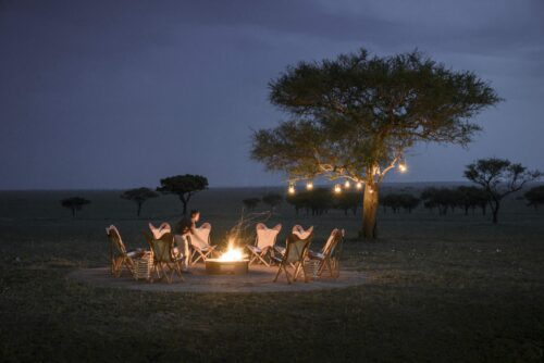 chairs around a campfire with lanterns in a distant tree