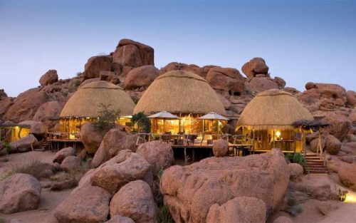 camp built into the red desert rocks in namibia