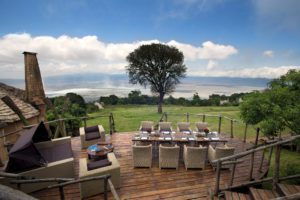 al fresco dinner table on wooden decking overlooking the Ngorongoro Crater with blue skies above