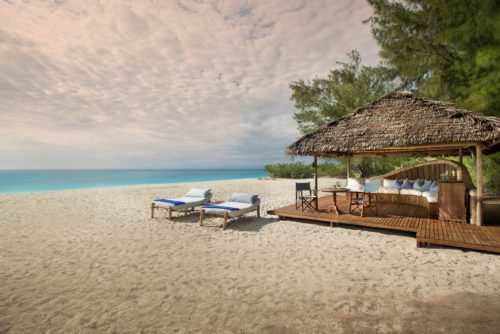 private cabana and lounge chairs on the sandy beach along the Indian Ocean