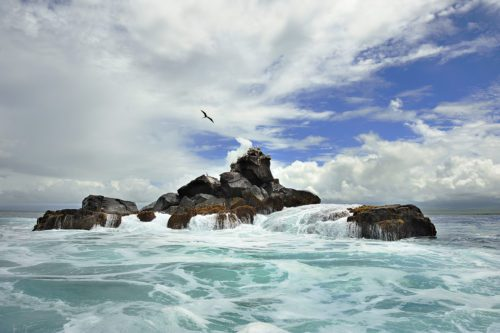ocean waves crashing on a rock with blue sky