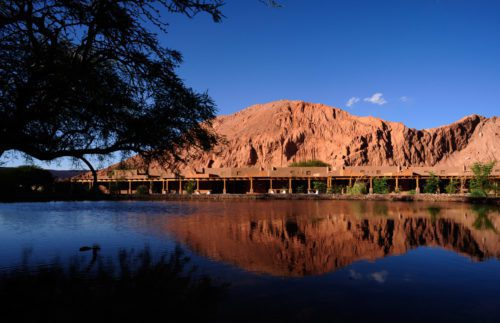 view of a lodge across water with red mountains behind