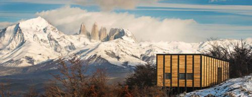 snowy mountains with wooden lodge