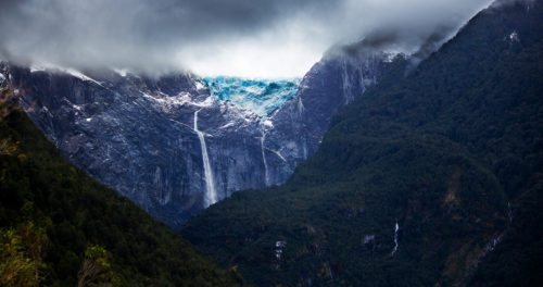 waterfall down a tall mountainside in aysen chile