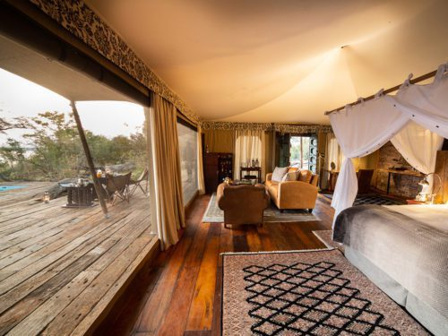 interior of mpala jena camp featuring wood floors, rugs, and a four poster bed