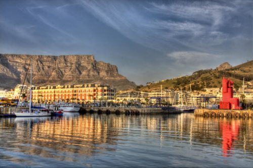 lit up property in a harbour with a mountain in the background seen on this luxury South Africa safari