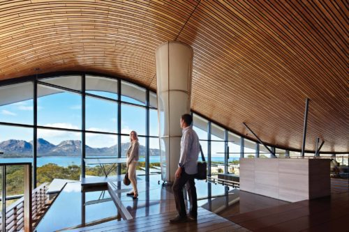 undulating roof and wall of windows with two people looking out at the views over wineglass bay