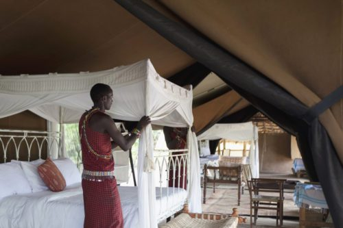 Maasai askari arranging the mosquito net inside a luxury safari tent in the Masai Mara