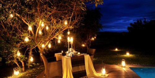 candlelit dinner in the bush beneath a tree filled with kerosene lanterns