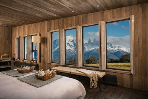 bed with glass windows and mountains
