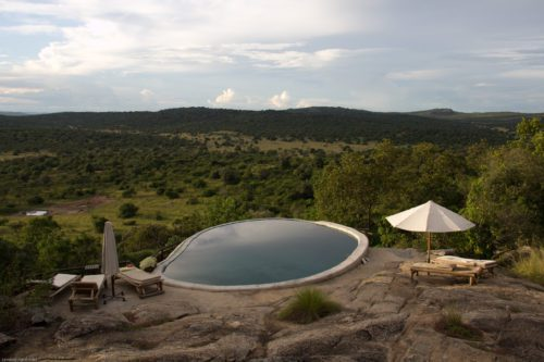 umbrella and lounge chair by the round pool at Mihingo Lodge overlooking the lush countryside of Lake Mburo