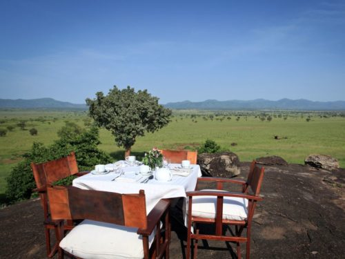 outside lunch table with white linens set up on a rocky outcropping overlooking the green savannah in Kidepo Valley