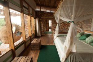 mosquito nets around the bed in the stone chalets at Kyambura Gorge Lodge in Uganda