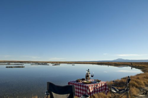 landscape at awasi atacama - picnic table overlooking the water
